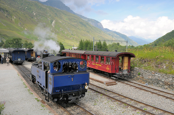 Furka cogwheel railway steam engine shunting at Realp station. Switzerland, Western Europe, Grimsel-/Furka region, Uri. The steam engine HG 3/4 No. 1 Furkahorn DFB 1 was built in 1913. With an engine power of 600 hp and a weight of 42 tons it manages a maximum speed of 45 km/h on adhesion rails and 20 km/h on cogwheel rails. Note: No releases available. --- Info: In 1914 the first steam trains started from Brig and reached Gletsch traveling along the river Rhone. In the following years the line was extended and finally connected in Disentis with the Rhätische Bahn in 1926. Although the Furka-Oberalp-Bahn was electrified in 1942, due to the extreme climate and the topography of this alpine area the trains could not run between Oberwald and Realp through the winter. So in the 1970's a modern tunnel was built for all year use. In 1983 the Furka Cogwheel Steam Railway Club was founded by railway enthusiasts to repair and maintain the original track and rolling stock. This included bringing back and restoring the original steam engines that were sold of to Vietnam in 1947. In late summer 2010 the historic steam link over the Furkapass was finally fully reestablished!