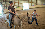An instructor works with a client in the horse therapy program at OUS Horse Park.