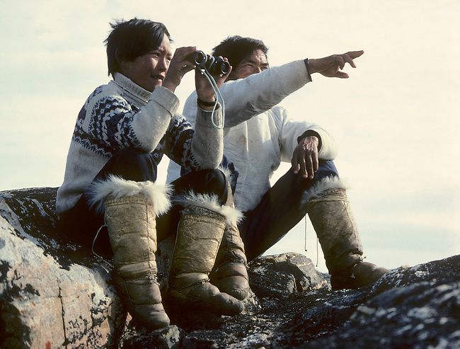 At a hunting camp an Inuit hunter his son scan the sea for Narwhals. They wear sealskin kamik (boots). Thule, Northwest Greenland.