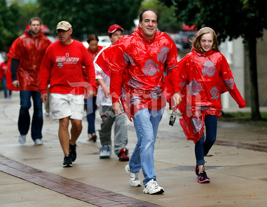 Braving the rain and wind, Eric Leasure and his 12-year-old daughter Abi of Galloway walk into Ohio Stadium wearing scarlet ponchos prior to the NCAA football game against Florida A&M in Columbus on Sept. 21, 2013. (Adam Cairns / The Columbus Dispatch)