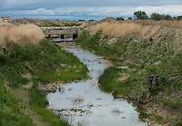 A canal near the Arkansas River in Crowley County, Colorado, Tuesday, May 17, 2016. Crowley County, once a thriving agricultural community with over 50,000 acres of farm land, sold it's water rights the City of Aurora for municipal use and now farms a little more than 5,000 acres of land. The result has seen dried and dead farm land and abandoned homesteads. Crowley County represents a dire look at how mismanaged water rights can have devastating effects on an already drought prone region.<br /> <br /> Photo by Matt Nager