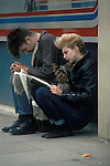 Punk couple reading a newspaper and with their pet dog.  London 1980s UK