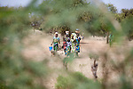 "In West Africa, certain villages have markets that ""assemble"" at regular intervals, such as weekly or every three days.  People from villages around the region come on market day to buy and sell food, livestock, and other goods and services.  Here, a group of women and children arrive by foot at the village market of Bourro in northern Burkina Faso."