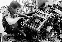 China. Province of Guangdong. The village of Beilin is part of the town of Guiyu. A male worker, seated on a an old discarded computer, takes down by hand electronic components and printed and integrated circuits of an old xerox machine. The various parts will be recycled for its metals, electronic components, chips,...© 2004 Didier Ruef