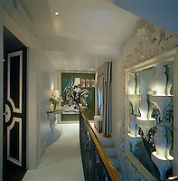 The narrow landing showcases a contemporary artwork and a collection of ceramic vases