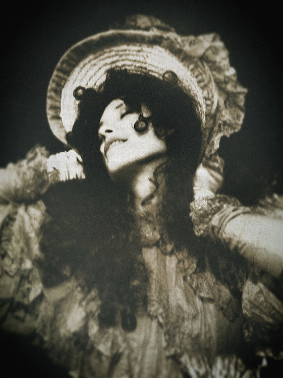 A woman in a victorian outfit, curly dark hair and a hat, posing in a lazy manner , closed eyes and a  delightful expression.