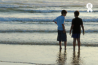 Two boys standing in water on beach, rear view (Licence this image exclusively with Getty: http://www.gettyimages.com/detail/200476767-001 )