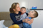 Raeda Firas hugs her 4-year old son Luis (right) as he gets ready to leave home in the morning to attend a church-run preschool in Ankawa, Iraq. Her younger son Yusef is in the middle. The Christian family was displaced from Mosul by ISIS in 2014, and live in a church-provided modular home.
