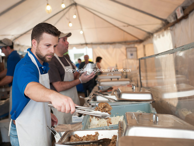 WATERBURY, CT-8 May 2015-050815EC04-  Andrew Thompson selects meat while behind him Jim Koulouris packs vegetables into a busy line of gyro assembly. Friday marked the opening day of Waterbury's 43rd Annual Greek Festival. Holy Trinity Greek Orthodox Church along Chase Parkway hosts the event, which includes food, music, jewelry, and other traditional items. The festival runs through Sunday. Erin Covey Republican-American