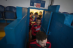 The players crowd out of the dressing rooms before Port Talbot Town played host to Caerau Ely (in red) in a Welsh Cup fourth round tie at the Genquip Stadium, formerly known as Victoria Road. Formed by exiled Scots in 1901 as Port Talbot Athletic, they competed in local and regional football before being promoted to the League of Wales  in 2000 and changing their name to the current version a year later. Town won this tie 3-0 against their opponents from the Welsh League, one level below the welsh Premier League where Port Talbot competed, watched by a crowd of 113.
