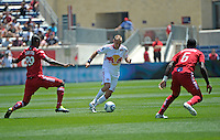 New York midfielder Joel Lindpere (20) looks for room to dribble while being defended by Chicago defenders Yamith Cuesta (89) and Jalil Anibaba (6).  The Chicago Fire tied the New York Red Bulls 1-1 at Toyota Park in Bridgeview, IL on June 26, 2011.