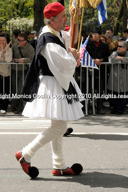 Greek Parade in New York City. An older man in costume and holding flags, walks in the Greek Parade in New York City.
