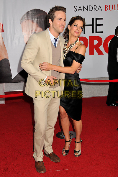 "RYAN REYNOLDS & SANDRA BULLOCK.""The Proposal"" Los Angeles Premiere held at the El Capitan Theatre, Hollywood, CA, USA..June 1st, 2009.full length silk satin dress grey gray peep toe shoes snakeskin strap black pearl silver gold necklaces beige suit sweater jumper off the shoulder arm around waist hug embrace .CAP/ADM/BP.©Byron Purvis/AdMedia/Capital Pictures."