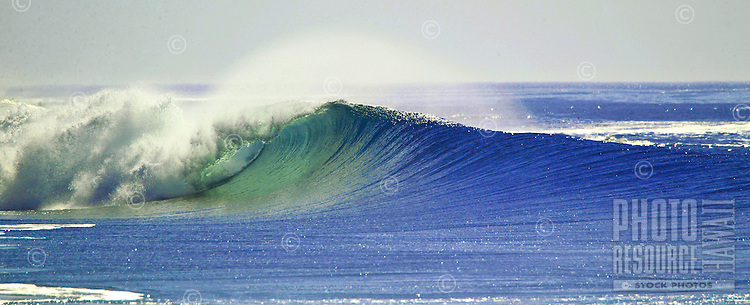 large sets of waves break along the tropical island coast