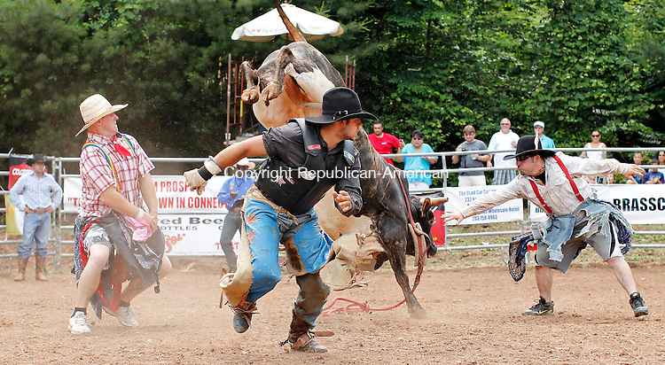 Prospect, CT-05, June 2010-060510CM11 Gustavo Dias, of Brazil gets out of the way of a bull after riding for a short time, during the Man Vs. Beast bull riding competition.  The event, held at Senior Poncho's in Prospect, featured top PBR riders from the world circuit.  The event will run again Sunday, from 2-4pm and will feature approximately 32 cowboys.  --Christopher Massa Republican-American
