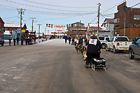 Rookie Dave DeCaro runs down Front Street into the finish chute in Nome during the 2010 Iditarod