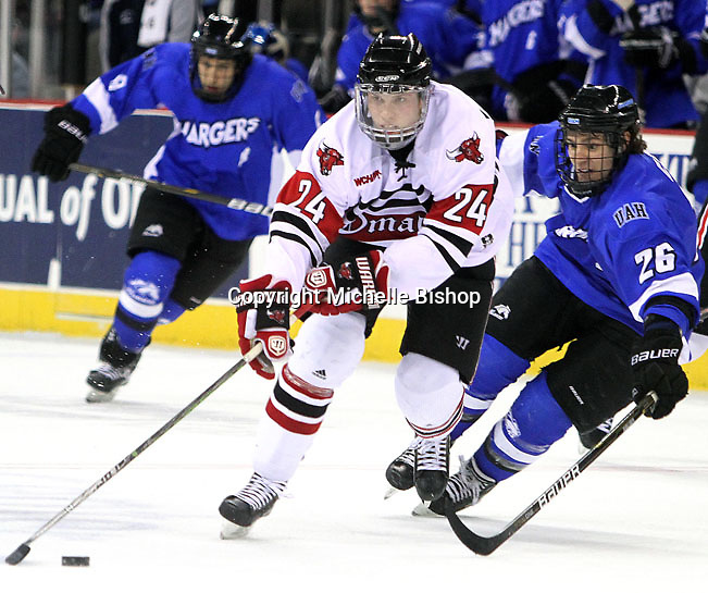 University of Nebraska Omaha's Bryce Aneloski controls the puck while being pressured by UAH's Justin Cseter. UNO beat Alabama-Huntsville 4-0 Friday night at Qwest Center Omaha.  (Photo by Michelle Bishop)