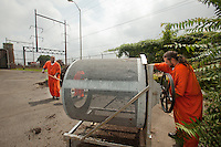 E'Ton Littlepage shovels compost to be filtered into the screener while Shawn O'Hanlon turns the crank. The screener, built by the prison maintainence department out of an old clothing dryer, filters out the trash and wood chips that did not break down and drops the pure filtered compost on the ground below.