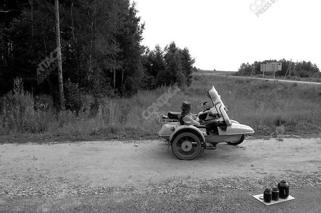 A man waited in the sidecar of his motorcyle at the roadside near the town of Spas Klepky, Ryazan region, to sell blueberries he had picked, part of common way for people in the countryside to make extra money, selling food to motorists often heading to nearby cities, here those on the way to Moscow. Russia, July 23, 2008.