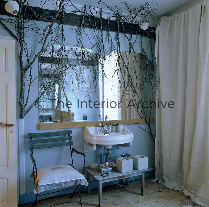 One wall of a simple bathroom decorated with bare branches