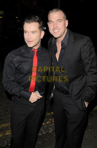 STEPHEN GATELEY & ANDY COWLES.Christopher Biggins' 60th birthday party, Landmark hotel, Marylebone Road, London, England. .December 15th, 2008 .half 3/4 length black suit red tie partner couple.CAP/CAN.©Can Nguyen/Capital Pictures.
