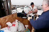 Volunteers take Linwood Fiedler's food drop bags from his truck into a warehouse where they, sort, weigh, and stack the mushers tens of thousands of pounds of food and gear for the 22 checkpoints.   Iditarod 2009