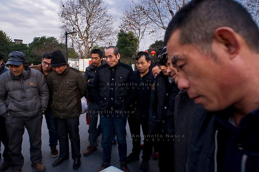 Hangzhou, Cina, 4 marzo, 2015. Un gruppo di uomini osserva un artista di strada in una piazza del centro storico della citt&agrave;.<br /> People look on a street artist in a square in downtown