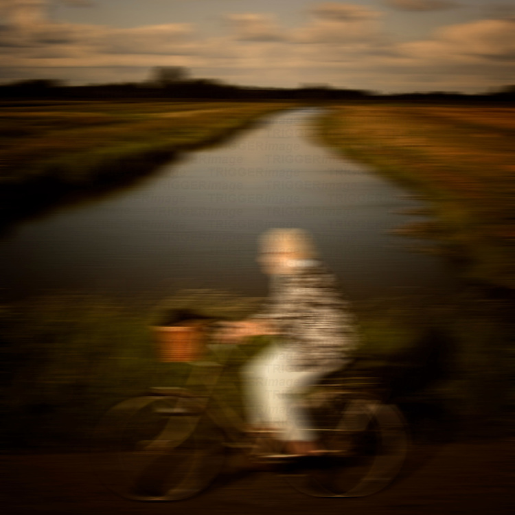 an old woman riding on a bicycle on the country by a river