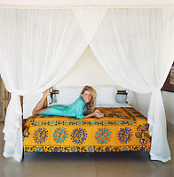 Portrait of Charlene de Ganay reclining on her four-poster bed