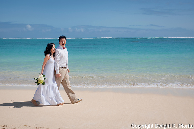 Asian bride and groom stroll side by side on Lanikai beach as they look forward to their life as a married couple following their wedding.