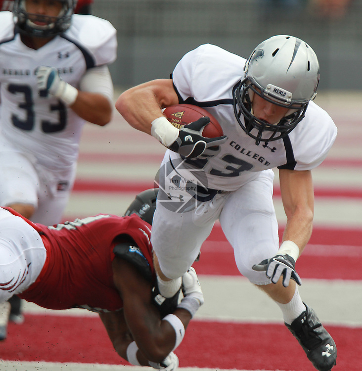 Lindenwood University's T.J. Holliam (14, left) tackles Menlo Oaks player Robert Gehre (83) in first half action during the Lindenwood Homecoming game. The Lindenwood Lynx team hosted the Menlo College Oaks.