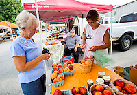 NWA Democrat-Gazette/JASON IVESTER <br /> Diane (cq) Turley (right) bags peaches on Wednesday, Aug. 5, 2015, for Janice Tucker of Rogers at the Rogers Farmers Market. The market is open on Wednesdays and Saturdays through October in dowtown Rogers.