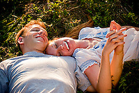 Young couple laying together in field