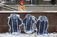 "Moscow, Russia, 04/02/2012..A woman enters a subway behind graffiti depicting Prime Minister Vladimir Putin as the three monkeys ""Hear no evil, see no evil, speak no evil"" watches as tens of thousands of demonstrators march in central Moscow and protest against election fraud and Prime Minister Vladimir Putin in temperatures of -20 centigrade. Organisers claimed an attendance of 130,000 despite the bitter cold."