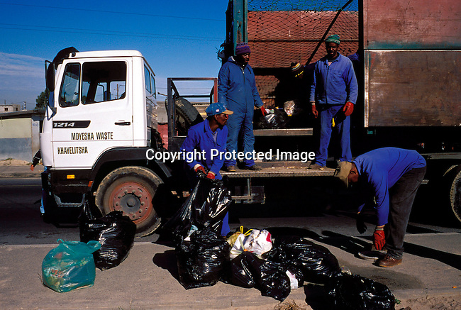 dienvpo00081 .Environment. Pollution. Workers picking up garbage from the street on July 21, 2001 in Site B Khayelitsha, a township about 35 kilometers outside Cape Town, South Africa.  Municipality services. Cleaning.  Waste, rubbish.©Per-Anders Pettersson/iAfrika Photos.