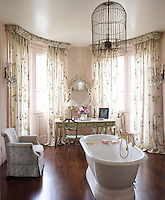 The walls of the elegant bathroom continue the faux bois paint effect of the master bedroom and the windows are decorated with floral curtains with a ruched pelmet
