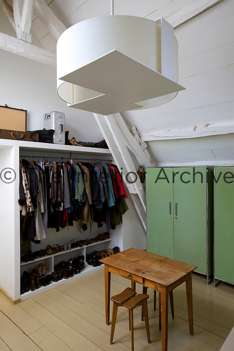 There is ample space in this dressing room with both built-in storage, open shelving and two antique Thonet wardrobes; the pendant light is an Eric Schmitt design