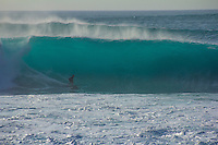 A surfer sets up for the barrel of a large wave at Pipeline, North Shore, O'ahu.