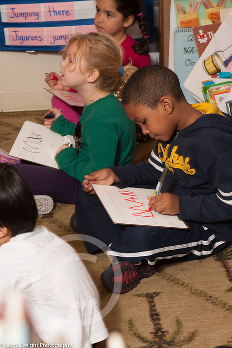 Education public school Kindergarten children sitting with dry erase boards practicing writing letters