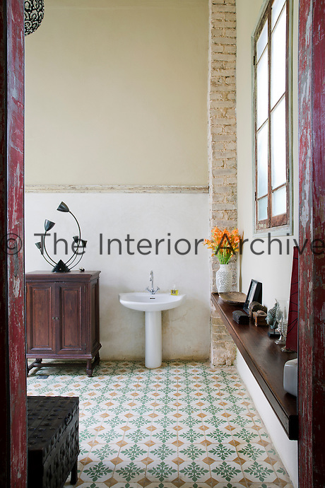 The spacious double-height bathroom features an original tiled floor, a theme throughout the house