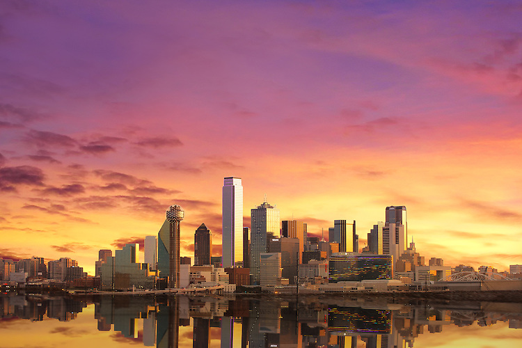 """Dallas Skyline at Sunrise with Reflection"" – Glowing in the early morning light, sunrise envelops the radiant Dallas skyline in incandescent warmth with colors of aureolin, saffron, lavender, wisteria, and marigold. In the foreground, a flooded Trinity River winds past the city, revealing a rarely photographed moment of the beautiful Dallas skyline. (Photo/Stephen A. Masker)"