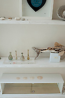 Simple white-painted shelving displays a collection of shells and pebbles, driftwood and antique glass phials