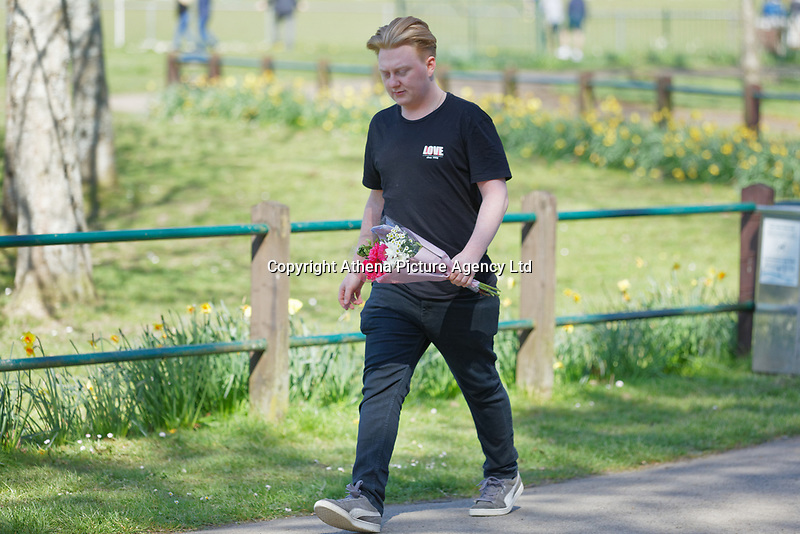 Pictured: A young man leaves flowers at Ystrad Mynach Park in south Wales, UK. Saturday 13 April 2019<br /> Re: A 13-year-old boy, named locally as Carson Price, , named lofcally as Carson Price, has died after being found unconscious in Ystrad Mynach Park, Caerphilly County, at about 7.20pm on Friday 12 April.<br /> The teen was taken to University Hospital of Wales in Cardiff where he was pronounced dead.