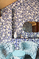 The walls of the entrance hall to the Collectors' Villa at Iniala is covered from floor to ceiling with blue and white plates, and a pair of armchairs in loosely draped pale blue leather