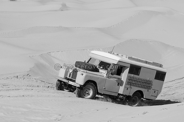 Africa, Tunisia, nr. Tembaine. Desert traveller Wolfgang driving an ex-army 1966 Land Rover Series 2a Ambulance through a sandfield with dunes close to Tembaine on the eastern edge of the Grand Erg Oriental. --- No releases available, but releases may not be needed for certain uses. Automotive trademarks are the property of the trademark holder, authorization may be needed for some uses.  --- Info: Image belongs to a series of photographs taken on a journey to southern Tunisia in North Africa in October 2010. The trip was undertaken by 10 people driving 5 historic Series Land Rover vehicles from the 1960's and 1970's. Most of the journey's time was spent in the Sahara desert, especially in the area around Douz, Tembaine, Ksar Ghilane on the eastern edge of the Grand Erg Oriental.