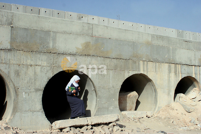 A Palestinian woman use a spillway to bypass the Israeli built controversial separation barrier in the al-Ram, northern of Jerusalem city. The spillway is used by Palestinians to cross the separation barrier when the Israeli Army closes the access gates of the wall.