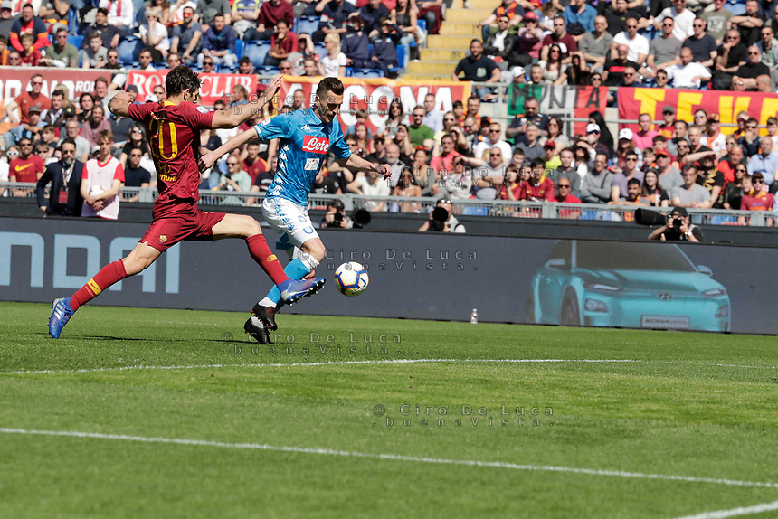 Arkadiusz Milik of Napoli  shoots and scores during the  italian serie a soccer match, AS Roma -  SSC Napoli       at  the Stadio Olimpico in Rome  Italy , March 31, 2019