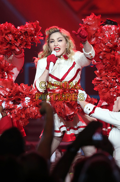 Madonna (Madonna Louise Ciccone) .Madonna performs at The Grand Garden Arena inside the MGM Grand Hotel and Casino, Las Vegas, Nevada, USA, .13th October 2012..music concert gig show live on stage performing half length red white cheerleader outfit costume collar gloves pompoms funny cheering microphone singing .CAP/ADM/MJT.© MJT/AdMedia/Capital Pictures.