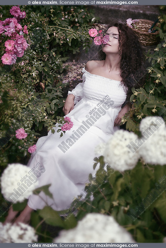 Romantic sensual portrait of a young woman smelling roses lying in white summer dress on stairs in a garden