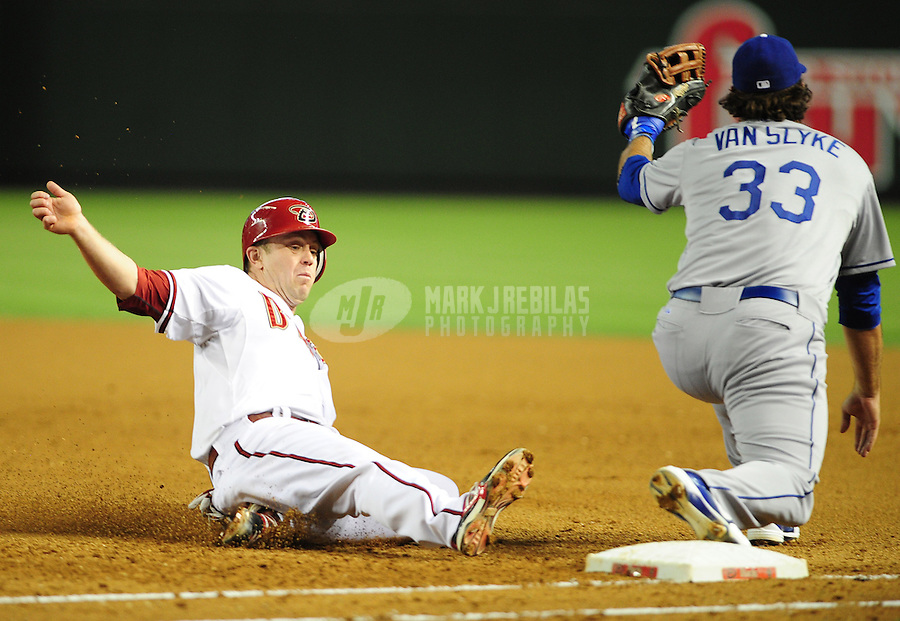 May 21, 2012; Phoenix, AZ, USA; Arizona Diamondbacks second baseman Aaron Hill slides back into first base on a pop fly in the fourth inning ahead of the ball to Los Angeles Dodgers first baseman Scott Van Slyke at Chase Field.  Mandatory Credit: Mark J. Rebilas-